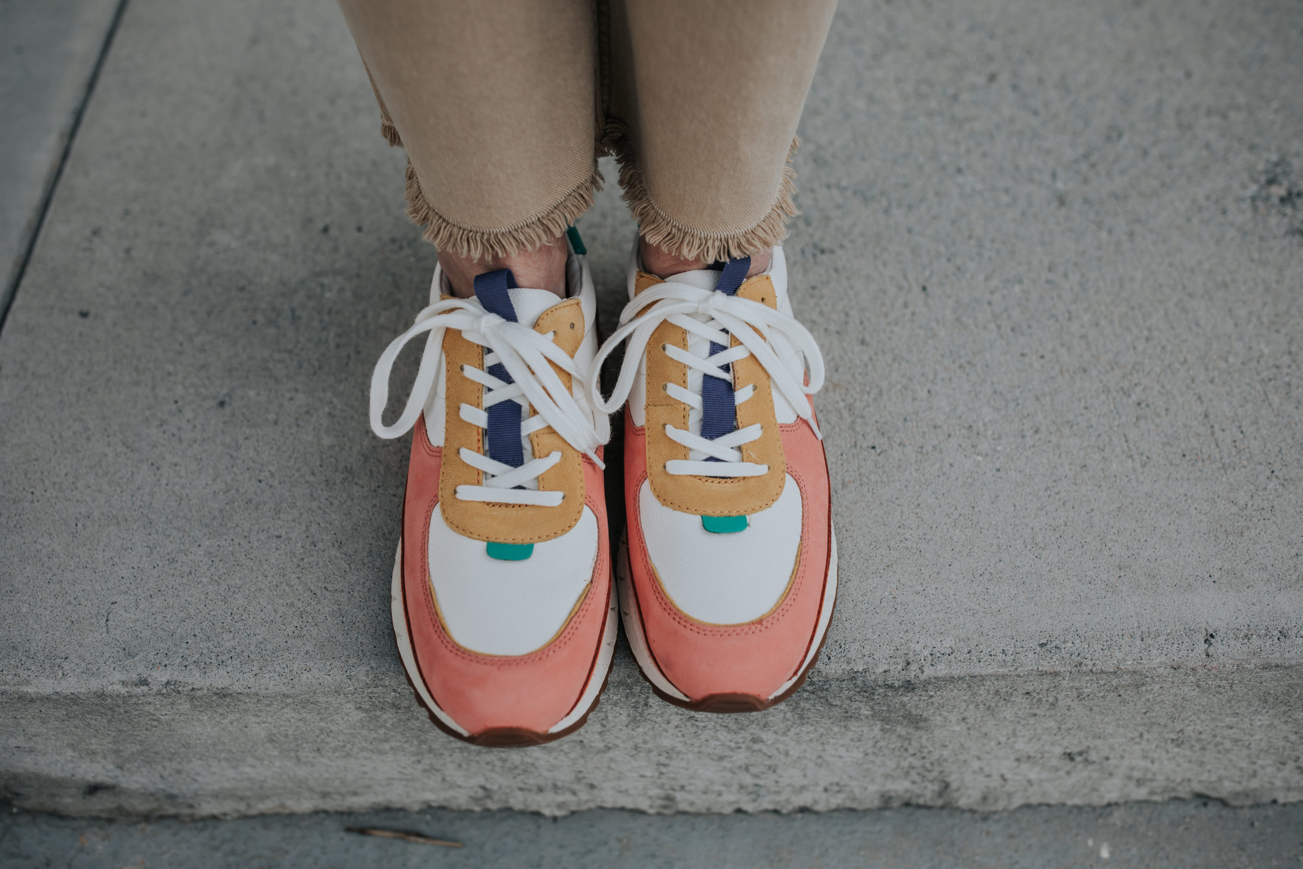madewell t shirt weekend blue denim longsleeve over the t shirt, blue round oversized sunglasses, color block tennis shoes from madewell and khaki pants paired with a straw purse that features an orange flap and gold embellishments