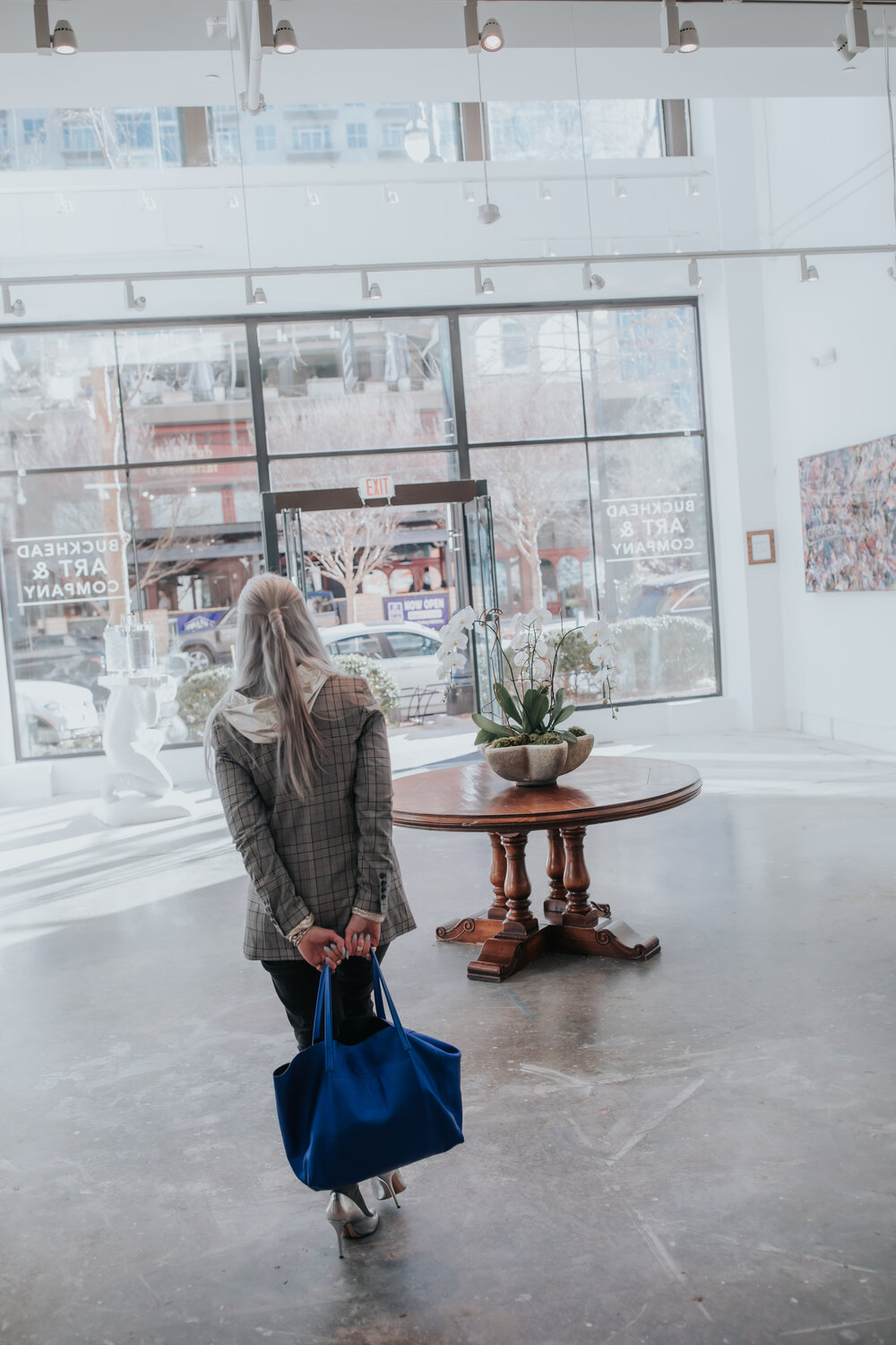 lisa in a gallery in atlanta wearing a tweed jacket with silver heels and socks with a blue bag