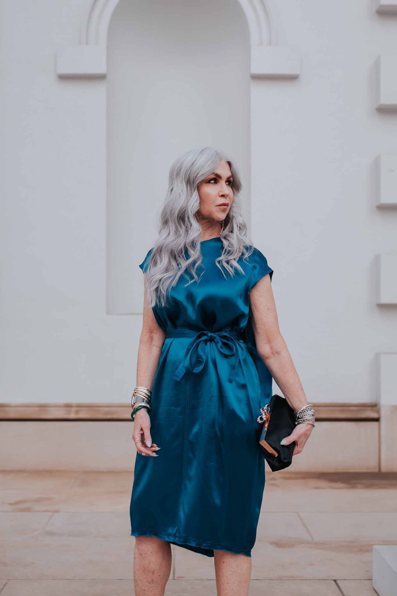 lisa in a blue silk below the knee formal wedding guest dress with dangling colorful earrings and creme pumps, and a black clutch